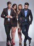 Mulheres elegantes que estão atrás de seus homens Fotos de Stock Royalty Free