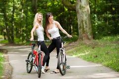 Mulheres em bicicletas em um parque Imagem de Stock Royalty Free