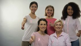 Mulheres em camisas cor-de-rosa com a fita do câncer da mama que mostra os polegares acima na câmera filme