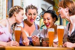 Mulheres em cartões de jogo bávaros do bar Fotografia de Stock Royalty Free