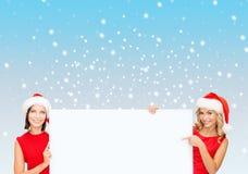Mulheres em chapéus do ajudante de Santa com placa branca vazia Foto de Stock