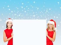 Mulheres em chapéus do ajudante de Santa com placa branca vazia Fotos de Stock Royalty Free