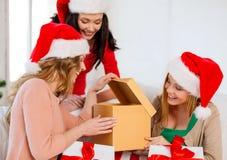 Mulheres em chapéus do ajudante de Santa com muitas caixas de presente Fotos de Stock Royalty Free