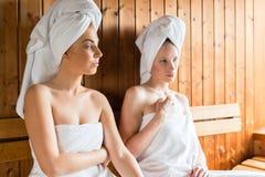 Mulheres em termas do bem-estar que apreciam a infusão da sauna Imagem de Stock