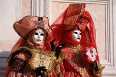 Mulheres em trajes coloridos e máscaras que levantam no carnaval em Veneza, Itália Imagem de Stock