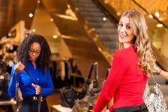 Mulheres em uma alameda de compra com decoração do Natal fotos de stock