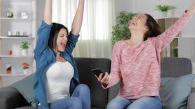 Mulheres entusiasmados que leem boas notícias no telefone em casa video estoque