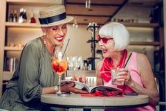 Mulheres envelhecidas alegres que leem um compartimento junto imagens de stock royalty free