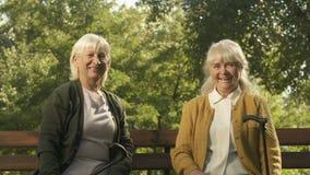 Mulheres envelhecidas felizes que aumentam acima as bengalas, sentando-se no banco, gesto do vencedor filme