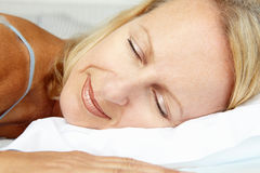 Mulheres envelhecidas meados de que encontram-se e que dormem em uma cama Imagem de Stock Royalty Free