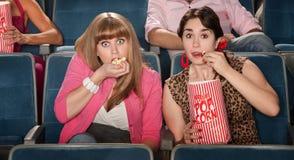 Mulheres espantadas que comem a pipoca Imagem de Stock Royalty Free