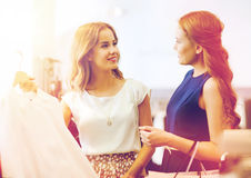 Mulheres felizes com os sacos de compras na loja da roupa Imagens de Stock Royalty Free