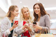 Mulheres felizes com smartphones e sacos de compras Fotos de Stock