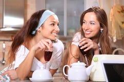 Mulheres felizes com vinho na cozinha fotografia de stock royalty free