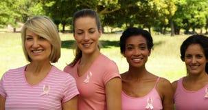 Mulheres felizes diversas que vestem o rosa para a conscientização do câncer da mama no parque video estoque