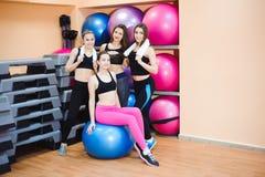 Mulheres felizes do grupo treinadas no gym usando o equipamento Retrato do grupo foto de stock royalty free