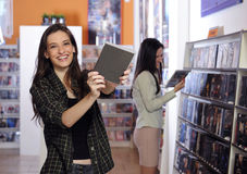 Mulheres felizes na loja rental video imagem de stock
