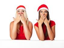 Mulheres felizes no chapéu do ajudante de Santa com placa branca vazia Foto de Stock Royalty Free