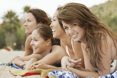 Mulheres felizes que encontram-se para baixo na praia foto de stock royalty free