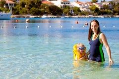 Mulher gravida feliz com a filha no mar Fotos de Stock
