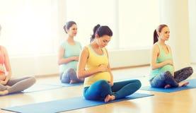 Mulheres gravidas felizes que exercitam a ioga no gym Imagens de Stock