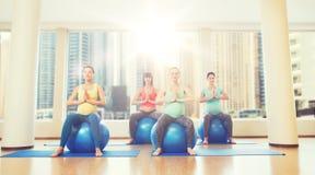 Mulheres gravidas felizes que exercitam no fitball no gym Foto de Stock