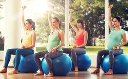 Mulheres gravidas felizes que exercitam no fitball no gym Imagens de Stock Royalty Free