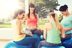 Mulheres gravidas felizes que sentam-se em bolas no gym Imagem de Stock