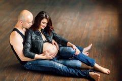 Mulheres gravidas novas com seu marido no estúdio Imagens de Stock Royalty Free