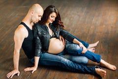 Mulheres gravidas novas com seu marido no estúdio Foto de Stock