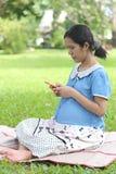 Mulheres gravidas que usam smartphones para procurar para obter informações sobre de Imagem de Stock Royalty Free