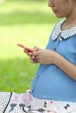 Mulheres gravidas que usam smartphones para procurar para obter informações sobre de Fotografia de Stock