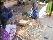 Mulheres indianas envelhecidas que fazem a seda com suas mãos imagens de stock