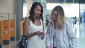 Mulheres jovens felizes com smartphone e sacos de compras conversando no shopping video estoque