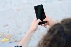 Mulheres latin novas que enviam a mensagem com smartphone imagens de stock royalty free