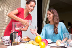 Mulheres latino-americanos bonitas que apreciam uma refeição home exterior junto imagem de stock