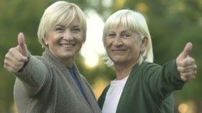 Mulheres maduras louras que sorriem in camera e que mostram os polegares acima, pensionista felizes vídeos de arquivo