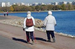 Mulheres mais idosas com bengalas nórdicas que andam no parque Kolom Fotos de Stock