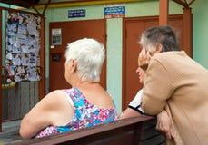 Mulheres mais idosas em um banco na entrada de um prédio de apartamentos imagem de stock