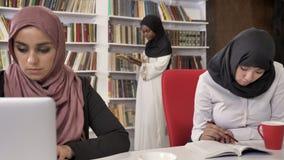 Mulheres muçulmanas novas no hijab que estudam na biblioteca, leitura e preparando-se para o exame, prateleiras com o fundo dos l filme
