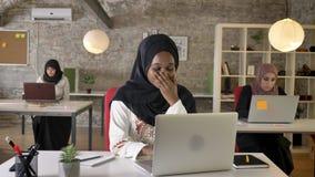Mulheres muçulmanas pretas novas no hijab que trabalha no portátil e no bocejo, cansados, o assento de três mulheres muçulmanas b vídeos de arquivo