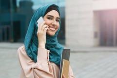 Mulheres muçulmanas que vestem o hijab usando o telefone celular foto de stock royalty free