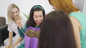 Mulheres muito caucasianas a olhar através de presentes dados à sua amiga grávida Quatro meninas em vestidos leves conversando vídeos de arquivo