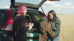 Mulheres multi-étnicos emocionais que embalam para a viagem por estrada video estoque