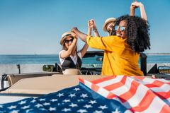 mulheres multi-étnicos que guardam as mãos ao sentar-se no carro com bandeira americana Foto de Stock