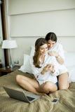 Mulheres na cama com portátil Fotos de Stock Royalty Free