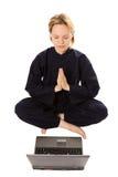 Mulheres na meditação do quimono no pose dos lótus com portátil Foto de Stock
