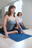 Mulheres na pose praticando do pombo da classe da ioga imagem de stock
