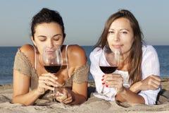 Mulheres na praia com vinho vermelho Imagens de Stock Royalty Free