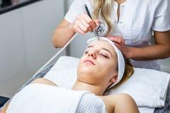 Mulheres no armário da cosmetologia O Cosmetologist está fazendo o procedimento para a moça Imagem de Stock Royalty Free